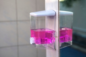 wall-mounted soap dispenser with pink liquid inside