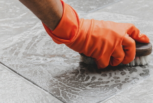 gloved hand scrubbing tile floor with brush