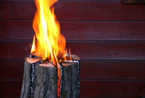 A tree stump against a wall or fence, flames emitting from the top of the stump
