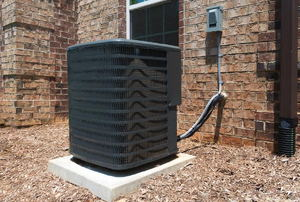 An air conditioning unit outside a brick house.