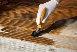 applying coat of deck stain