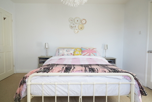 A modern bedroom with a queen-size bed and metal frame.