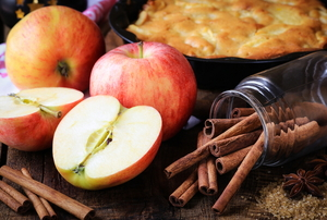 Red apples surrounded by cinnamon sticks and a pie in the background.