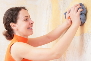 A woman wiping away wallpaper glue with a rag.