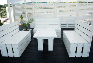 white wooden table on a deck surrounded by white wooden benches and fencing