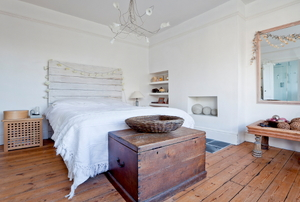 A white bedroom with a whitewashed headboard above the bed.