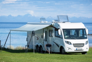 An RV with an awning parked by water