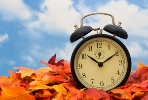 A clock sitting in a pile of fall leaves against a blue cloudy sky.