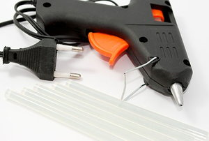 a black glue gun and glue sticks