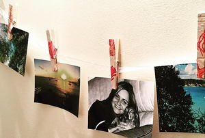 A garland of photos held on a string with decorated clothespins.