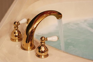 A gold-toned faucet running water into a bathtub.