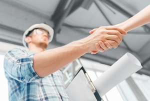 A contractor shakes hands with a woman.