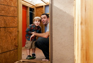 A father and son in a new, backyard playhouse