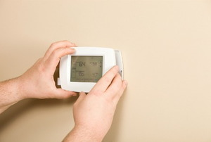 A person adjusting a programmable thermostat on the wall.