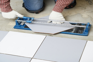 A man uses a ceramic tile cutter.