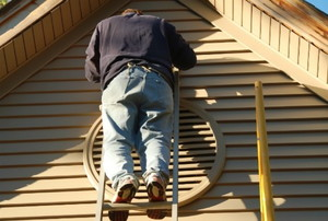 man on ladder facing vinyl siding of house