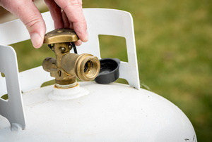 A man adjusts a propane regulator.