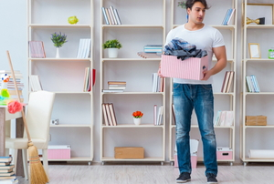person moving box full of home goods in room with open shelving
