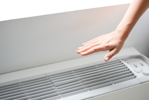 Someone using their hand to test the temperature of the air from an AC unit.
