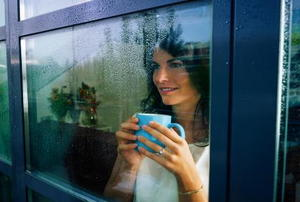 A woman holding a mug with two hands and looking out a rain-covered window.