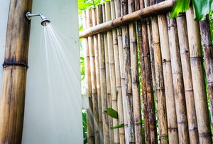 An outdoor shower with bamboo wall