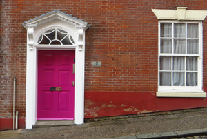 A pink door in a brick building.