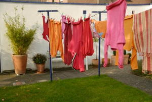 A clothesline in an urban backyard with clothes hanging to dry.