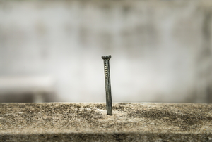 A nail driven into concrete.