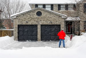 A homeowner shovels snow from his driveway.