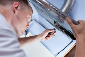A man works on a hood vent system.
