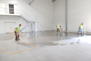 applying sealant to a concrete floor in a large building