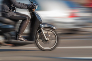 blurring image of rider on a scooter