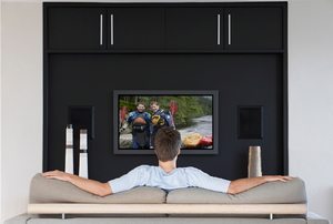 A man watching TV on his home entertainment center.