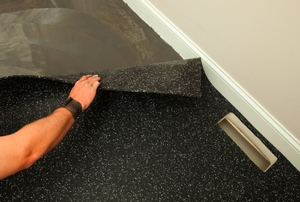 A worker installs a section of recycled rubber floor onto an adhesive covered concrete slab.