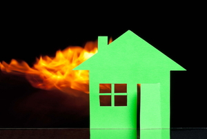 A green paper house with flames in the background.