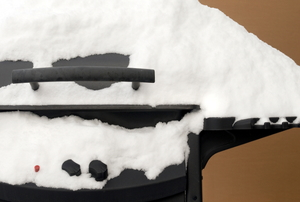 A BBQ covered in snow.