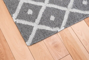 A gray and white patterned area rug laying on hardwood floor.