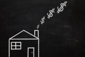 A house on a blackboard, with dollar signs emanating from its chimney.