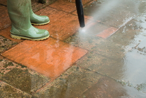 A pressure washer cleaning mildew off of a brick patio.