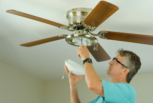 A man installing a ceiling fan.