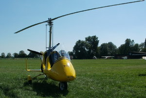 yellow gyrocopter on the grass