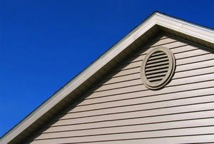 A gable vent on white siding.