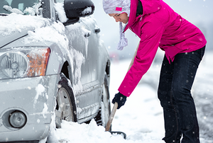 Woman shoveling snow to free her car on the road