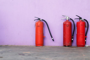 A trio of red fire extinguishers against a purple wall.