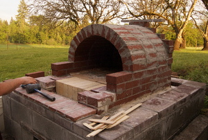 The construction of an outdoor brick pizza oven.