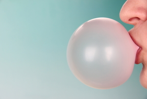 A person blowing a bubble with bubblegum against a blue background.