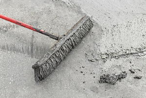 broom pushing on concrete surface