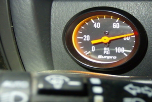 A dashboard oil pressure gauge reads high.