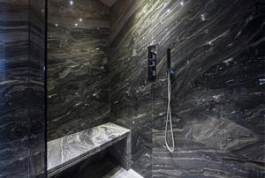 A shower with a frameless glass shower door.