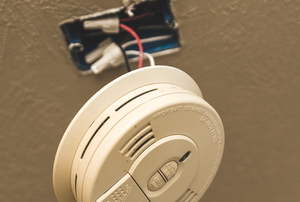 Smoke alarm mounted to a wood ceiling.